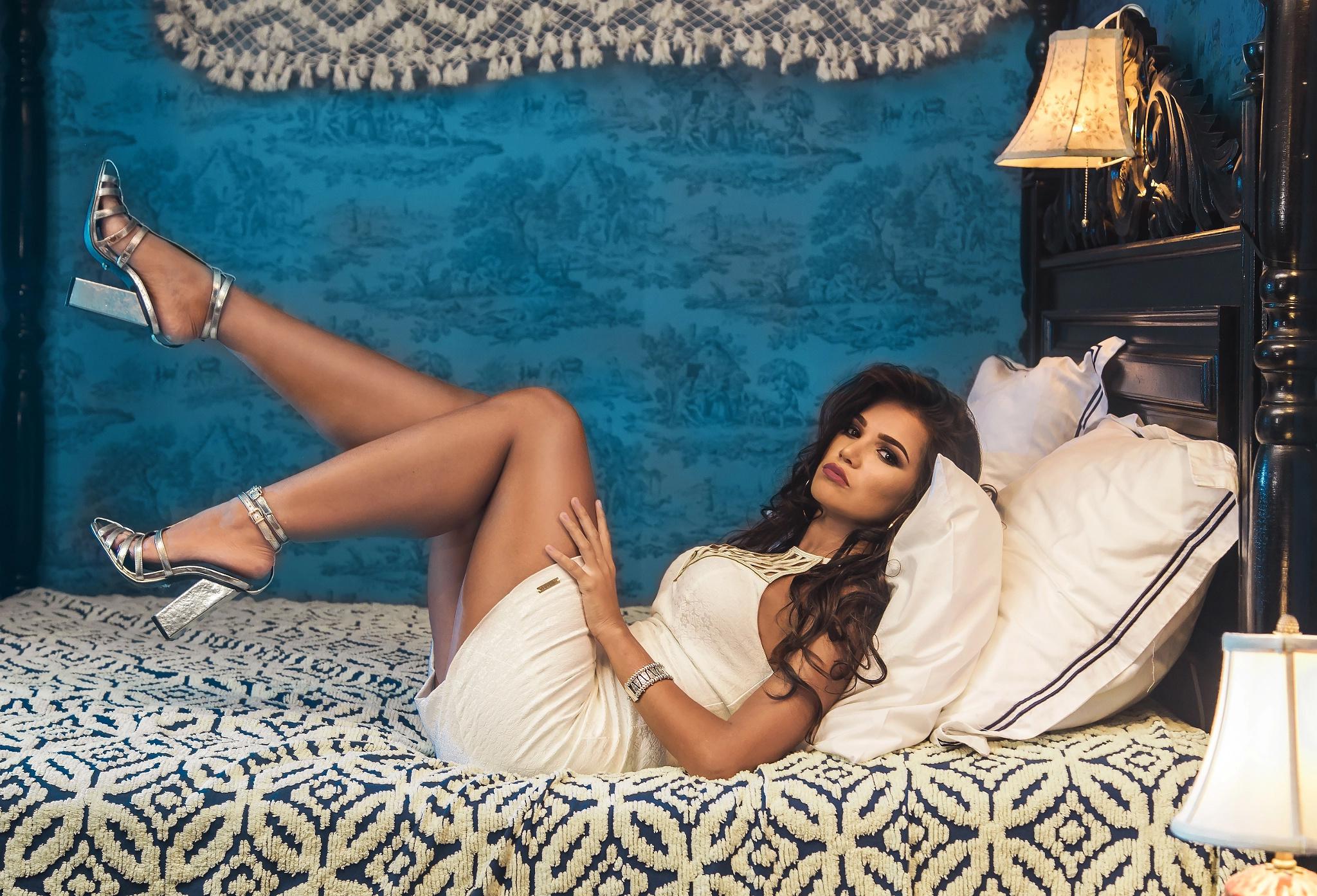 Голые девушка лежит в постели в босоножках