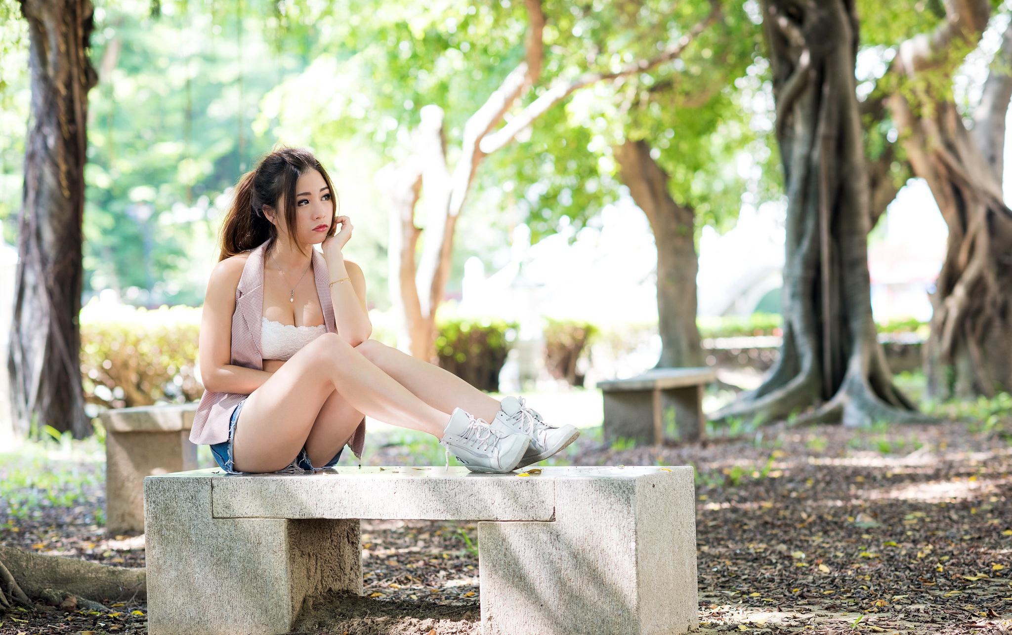 Женщина красивая сидит на скамье