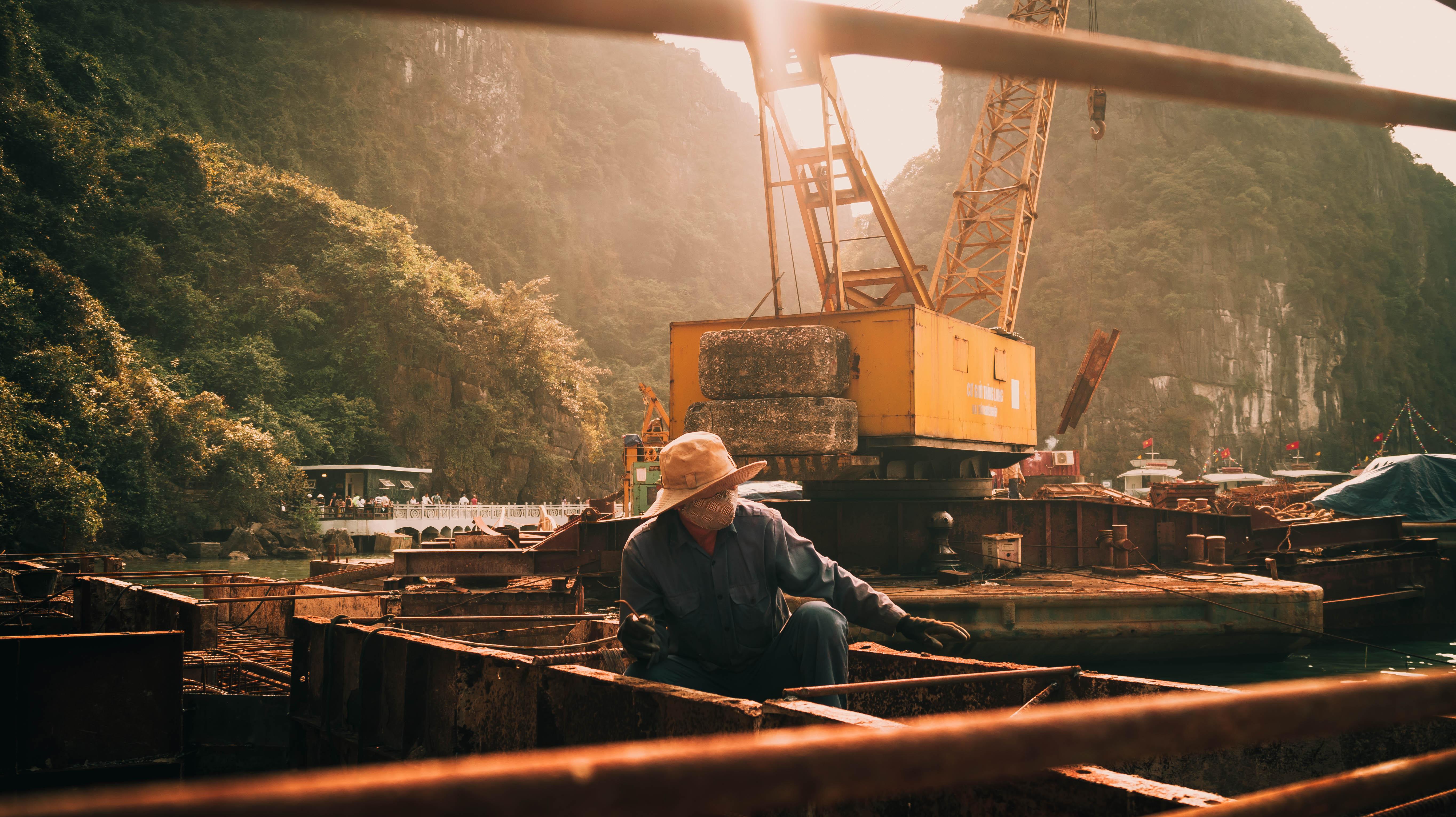 sun hats sun rays Vietnam workers cranes machine mountains Halong Bay  construction site men Asia 6ba7a0fd1b4