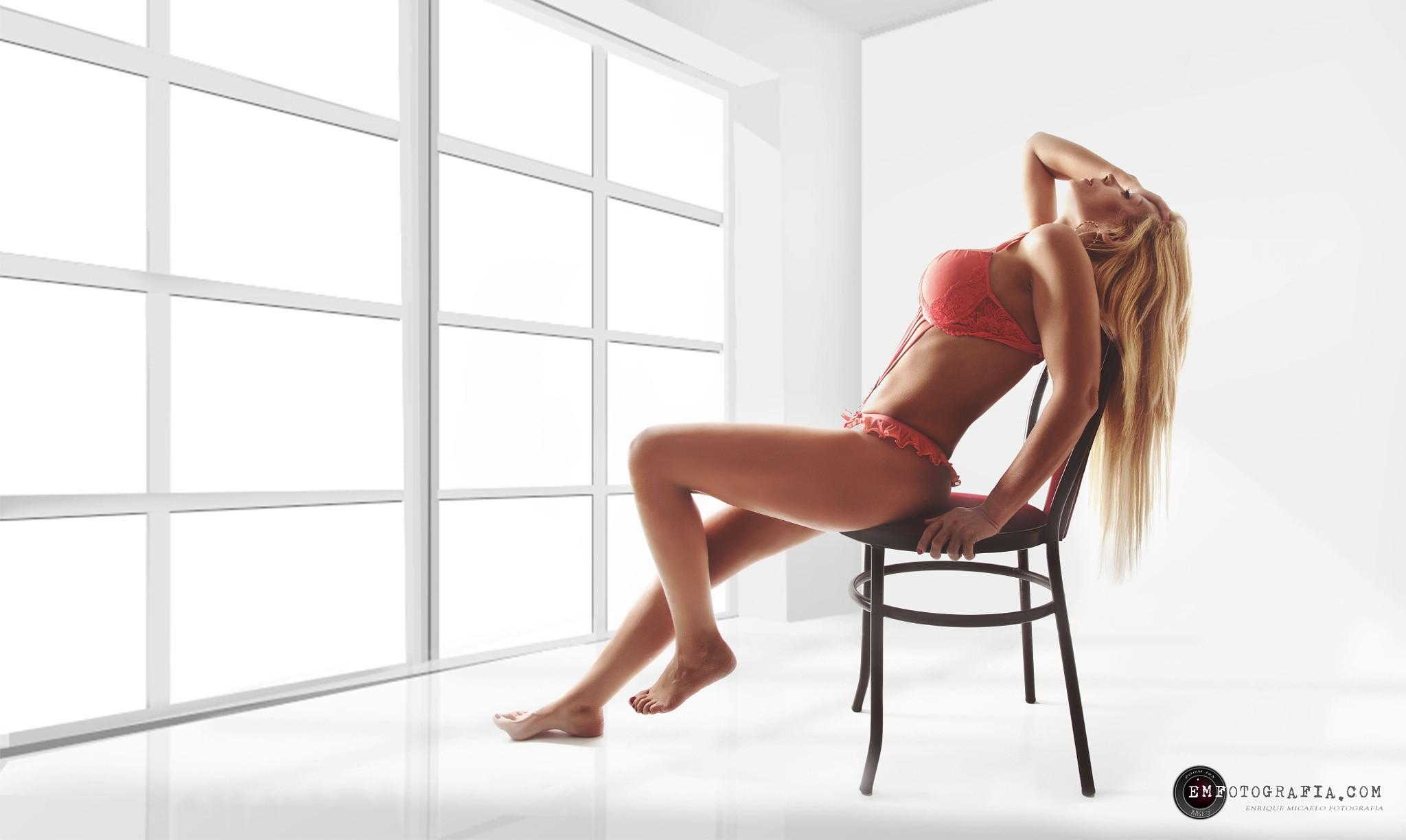 грудастая блондинка сидит на стуле голая