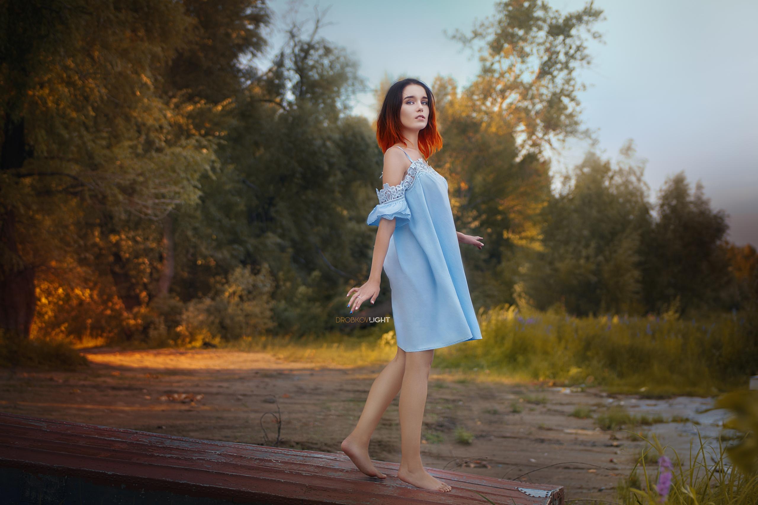 Другой рыжеволосая девушка в голубом платье начинает раздеваться
