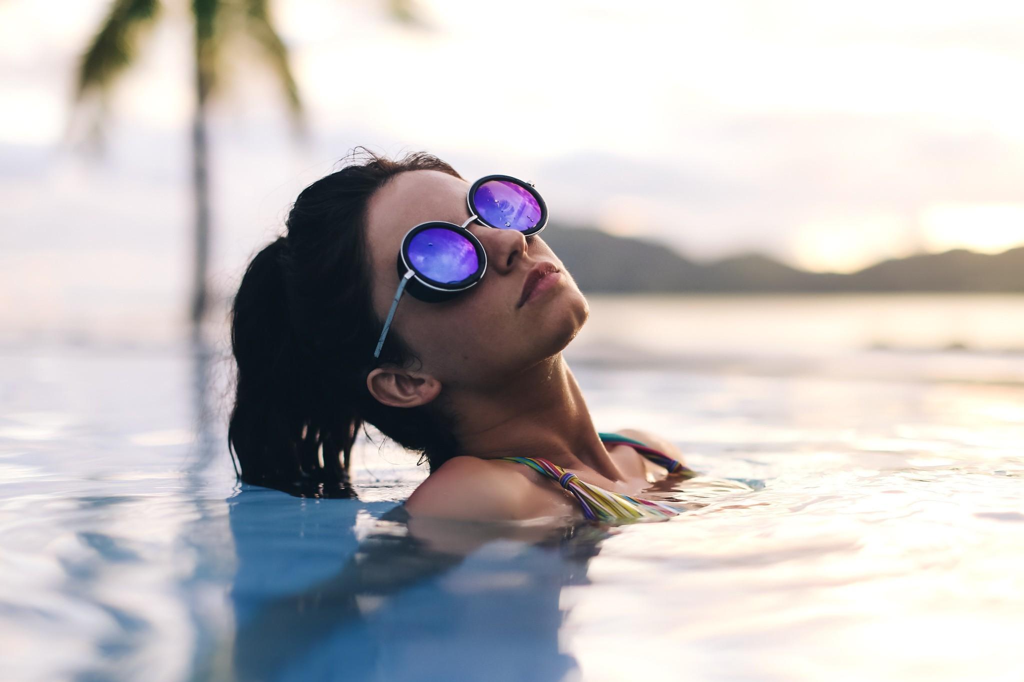 Девушка в солнечных очках на море фото