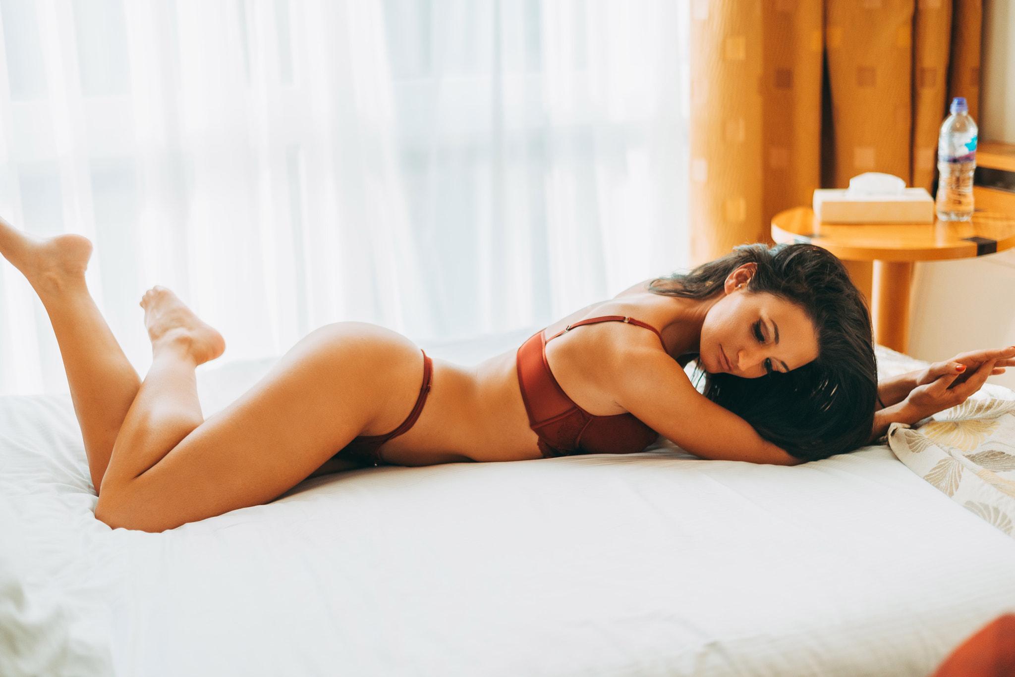 Девушка лежит в постели в босоножках 9