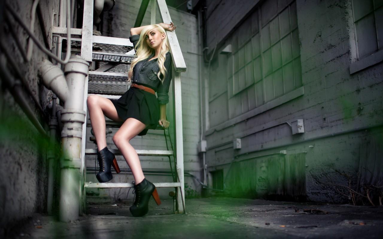 Девушка позирует на металлической лестнице фото